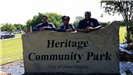 Volunteers by the Heritage Community Park Sign