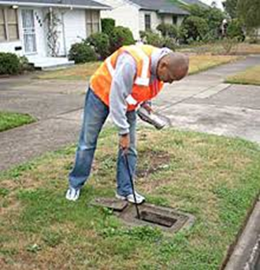 Technician Checking a Water Meter in the Ground